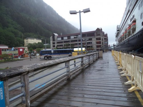 View down the side of the passenger ship. People boarding along a gangway in front.