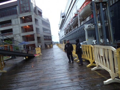 Two ferry terminal employees next to a gangway on to the ship.