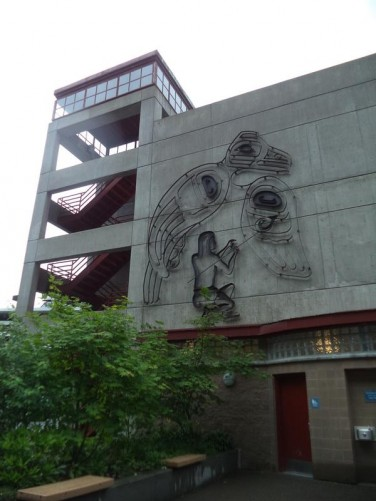 Concrete multi-storey car park with an artwork on the side that appears to depict a native Alaskan man and a bird.