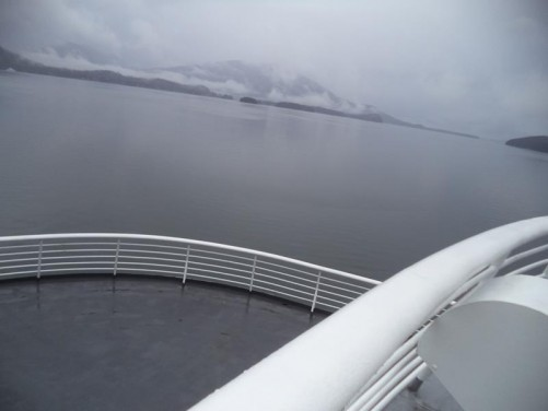 Onboard a passenger ferry docked at Juneau harbour. Looking from the stern of the ship along the Gastineau Channel. A mountain visible away in the distance. Tony and Tatiana on their way to Haines, south-east Alaska, travelling on the Alaska Marine Highway.