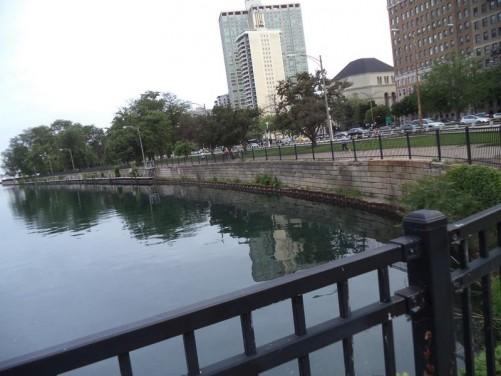 At the north end of Belmont Harbour in Lincoln Park. Facing North Lake Shore Drive running north-south along the side of the park. Tall residential apartment buildings along the road.