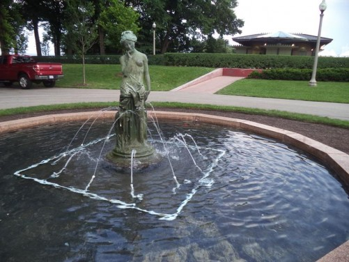 A pond with water spraying towards a female statue in the centre. Again in a public park.