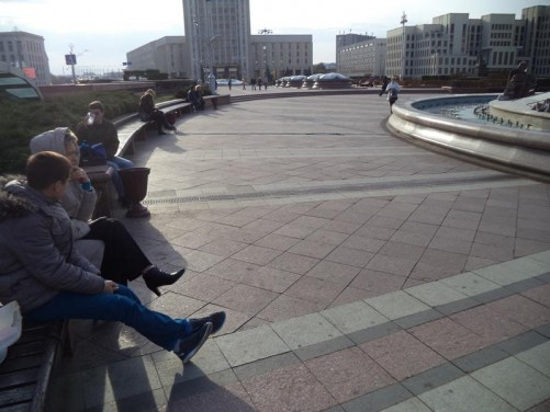 People sitting on benches in Independence Square. Next to a large circular fountain with water around the outside and a glass dome in the centre. Again the Belarusian State University and Government House buildings can be seen beyond.