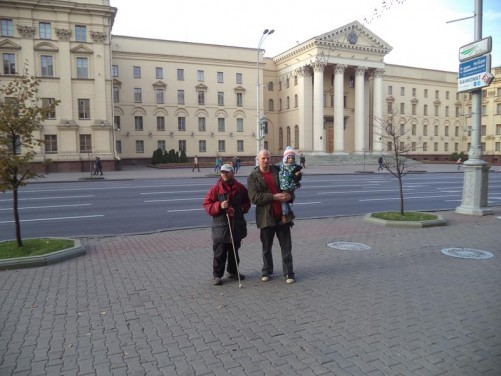Neoclassical KGB headquarters building on Independence Avenue. Tall entrance portal with Corinthian columns. Tony in the foreground with Aliaksej and his young son Dominik.