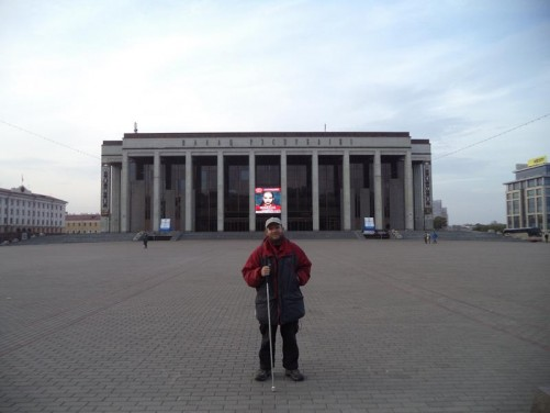 View across October Square to the huge austere concrete and glass front façade of the Palace of the Republic. This conference centre, concert hall and entertainment venue was erected between 1986 and 2001. Tony standing in front.