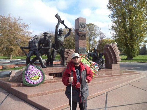 Tony in front of a memorial near Terespol Gate. It includes a bronze sculpture of three soldiers carrying out an attack.