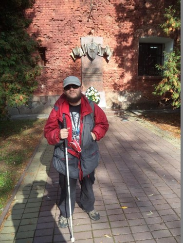 Tony in front of a memorial plaque attached to the brick inner walls. A wreath at the base.