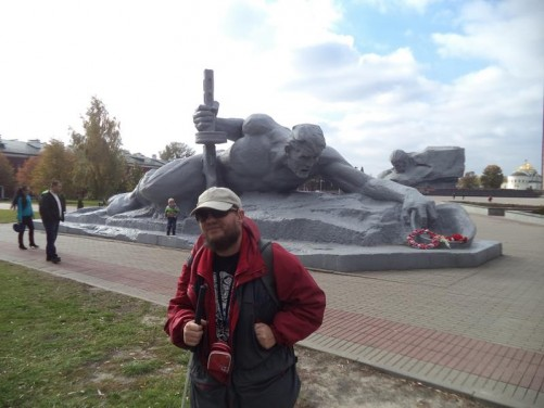 Tony by the monument 'Thirst'. It depicts a soldier creeping to water with a helmet in his hand.