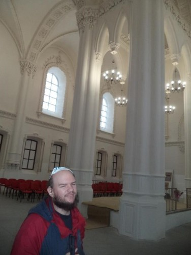 Inside the Great Synagogue of Hrodna. Tony wearing a skullcap (Kippah) as is customary. White painted walls and columns. The synagogue was first built from wood between 1576 and 1580 at Rabbi Mordechai Yaffe's invitation. It burnt down in 1902 and was rebuilt in a mix of eclectic and Moorish styles.