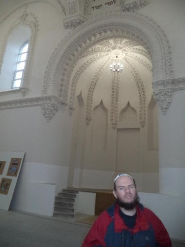 Tony in front of a large raised recess inside the synagogue.