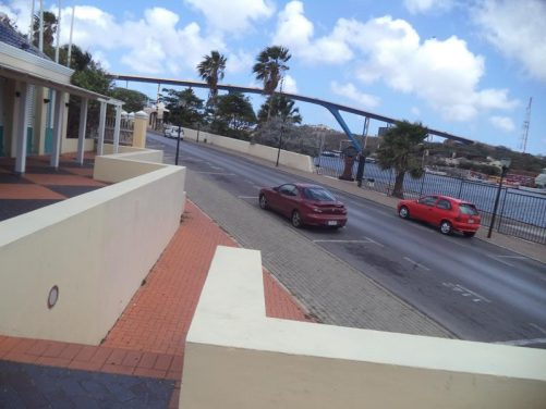 Roadside view from next to St Anna Bay in Otrobanda. In front is Queen Juliana Bridge (Koningin Julianabrug). This large four lane road bridge spans St Anna Bay and arches to a height of 56.4 metres (185 feet), allowing ships to pass underneath.