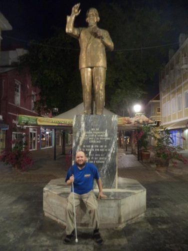 Tony sitting in front of a bronze statue of Dr Moises Frumencio Da Costa Gomez (1907–1966), the first Prime Minister of the Netherlands Antilles. He established the National People's Party, which negotiated self-government for Curaçao as part of the Netherlands Antilles in 1954.