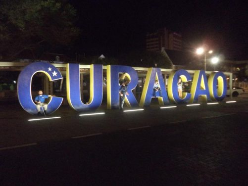 Huge free-standing blue and yellow letters spelling out the word Curaçao. People, including Tony, sitting inside the letters.