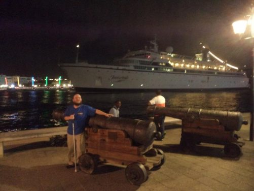 Tony touching one of a pair of historic canon on the Punda water front. A large cruise ship can be seen in St Anna Bay.