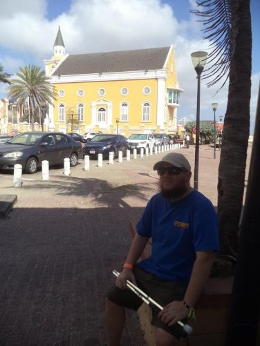 Tony near the Temple Emanuel in Punda. This yellow painted former synagogue opened in 1864 when a group of Reform Jews broke away from the older Mikve Israel congregation. The congregations reunited in 1964 and the building was eventually sold to the Netherlands Antilles government in 1989.