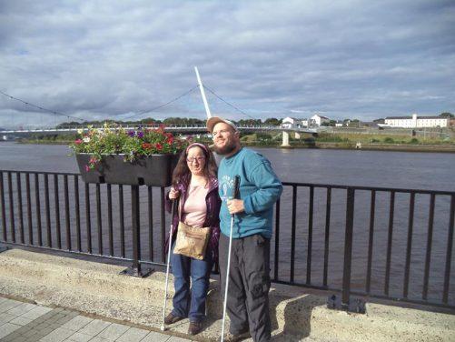 Tatiana and Tony by the River Foyle with the Peace Bridge behind.