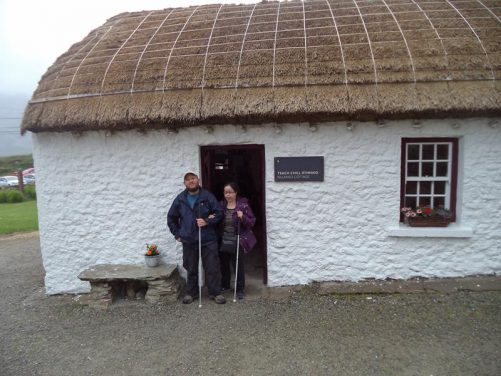 Outside 'Killaned Cottage' - painted white with a thatched roof.