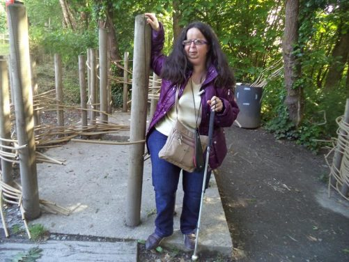 Tatiana next to a series of wooden posts that have been sunk into the ground. Lengths of cane-like material have been woven around them, perhaps demonstrating how prehistoric buildings were constructed.