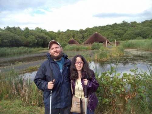 Tony and Tatiana in front of a lake with reeds growing in it. Beyond two round houses can be seen. These are standing on a crannog, which is a man-made island. These typically date from the early medieval period though some are much older.