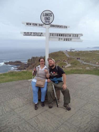 Tatiana and Tony sitting beside the famous Land's End sign. The signpost was erected in the 1950s.