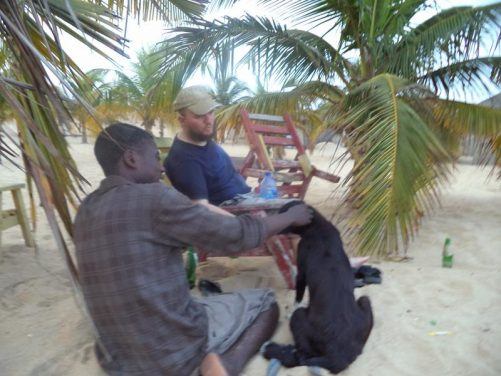 Tony sitting with Albert and a dog on Keta Beach, Ghana. Lots of palm trees. 23rd February.