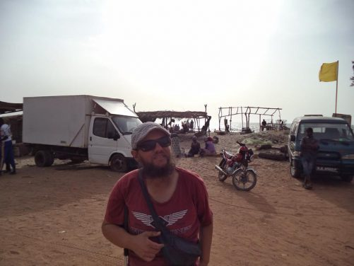 Tony on the edge of the beach. Parked vehicles, light wooden shelters and people sitting.