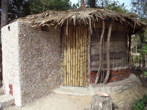 Outside a small hut with a thatched roof containing a bathroom.