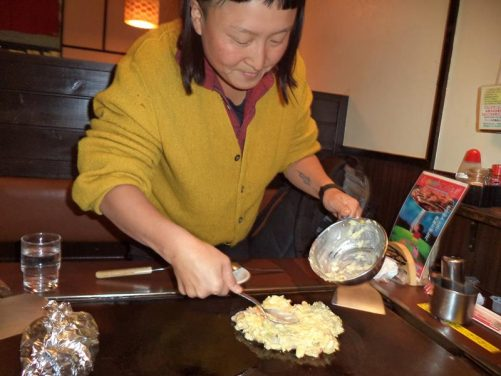 A Japanese lady named Umi preparing Okonomiyaki, which is a kind of Japanese pancake cooked on a hot plate on the table where customers sit in the restaurant.