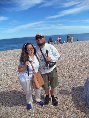 Tony and Tatiana on rocky Slapton Sands Beach. View out to sea behind.