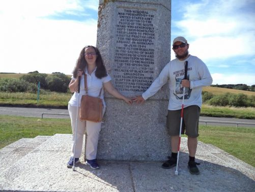 Close-up of Tony and Tatiana in front of a memorial at Slapton Sands.