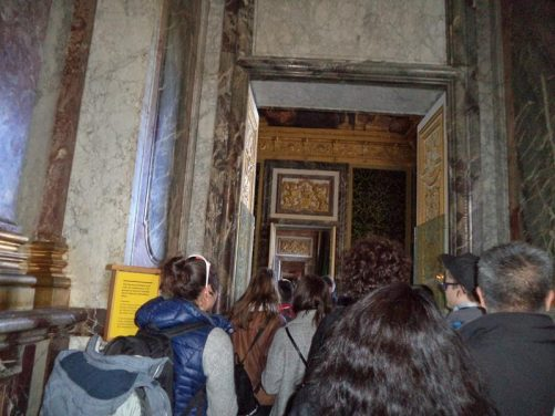 A group of visitors passing through a grand doorway inside the Palace of Versailles.