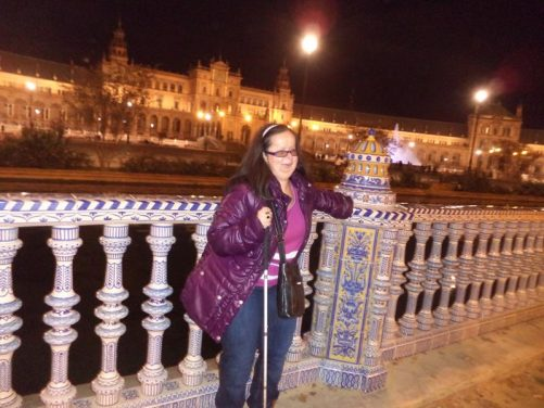 Tatiana by a decorative wall with balustrades in front of the moat at Plaza de España.