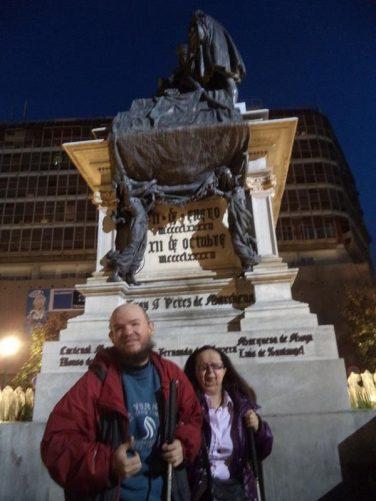 Tony and Tatiana next to the statue in Plaza Isabel La Catolica.