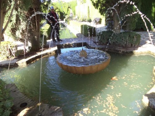 A fountain in the Generalife's Lower Gardens. Jets of water straying into a central fountain. A long rectangular pool extending beyond.
