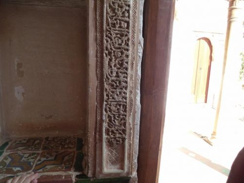 Intricate moulded-plaster decoration at the end of a wall and decorative ceramic tiles in an adjoining alcove within the Generalife.