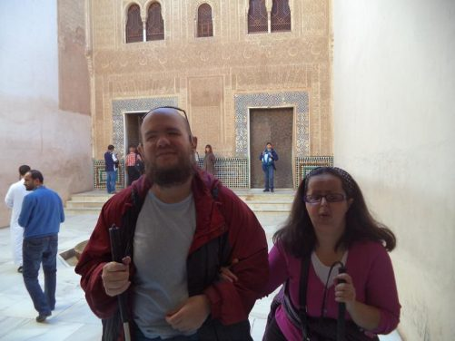 Tony and Tatiana in the Patio of the Gilded Room within the Nasrid Palace (Palacios Nazaries). A shallow fountain in the centre. The façade of the Comares Palace on the far side.