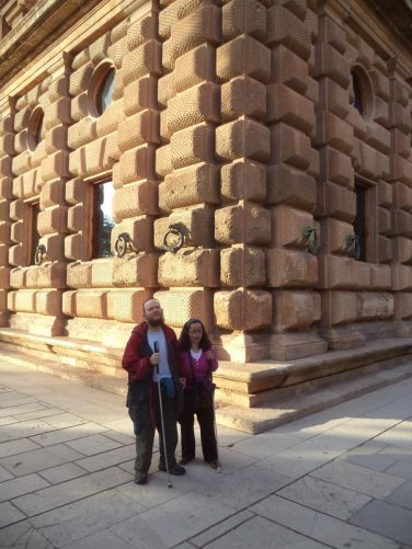 Tony and Tatiana outside the Palace of Charles V. They are standing at a corner of the towering 17 metre (56 feet) high outer wall. The palace is square-shaped with the sides measuring 63 metres (207 feet) in length. There is a circular courtyard in the centre of the building.