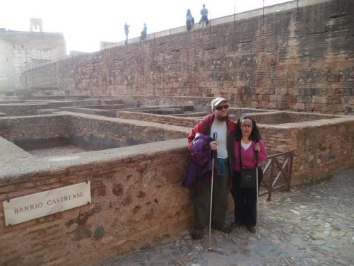 Tony and Tatiana by low walls marking the layout of former buildings that formed the Barrio Castrense (Castrense Neighbourhood), part of the Alcazaba.
