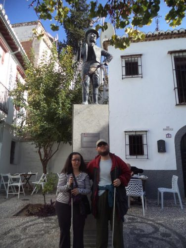 "Tatiana, Tony in front of a statue of a man with a strange hat, Chorrojumo, who was regarded as the ""king of the gypsies"". Taken in a small plaza in Sacromonte Neighbourhood."