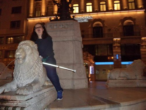 Tatiana sitting on a stone lion, part of the Lion Fountain. Jet of water coming out of the lion's mouth.