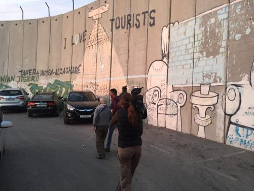 More filming at border. The wall is covered with murals and graffiti.