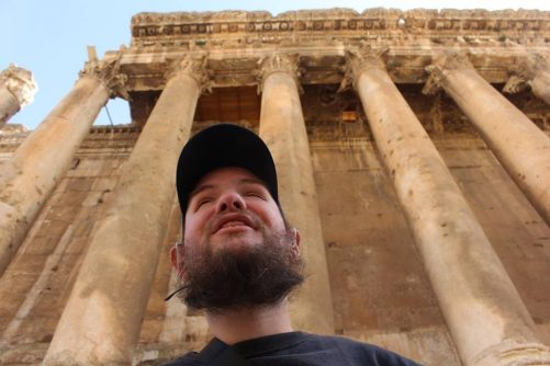 Tony outside the temple of Bacchus. Five stone columns towering behind.