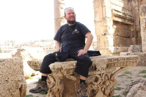 Tony sitting on an ancient table/platform at the Temple of Bacchus.