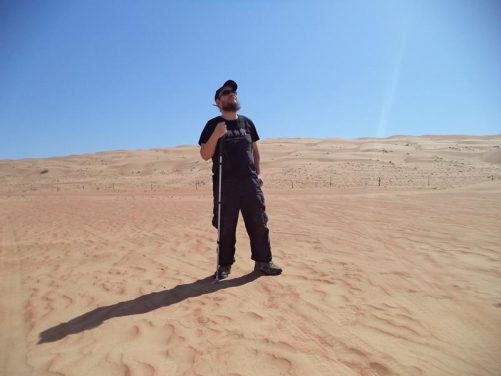 Tony in the desert. A dune rising up in the middle distance behind.