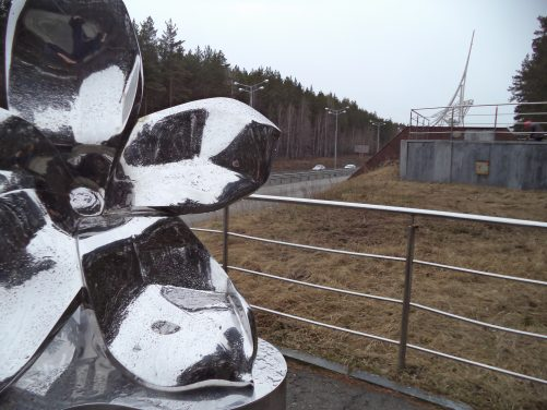 A large metal flower. An artwork near a monument at the dividing line between Europe and Asia, some 17 km west of Yekaterinburg. It stands next to a motorway with a pine forest in view on the far side.