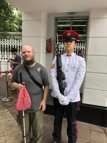 Tony standing alongside a ceremonial guard on sentry duty at the entrance to the Istana. The guard is holding a rifle with attached bayonet.