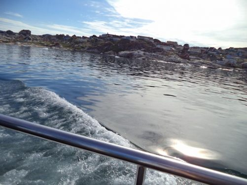 Looking into the harbour, which is in a narrow rocky bay. Small dispersed chunks of ice floating in the water. Part of the town can be seen beyond with houses spread out amongst rocks and grass.