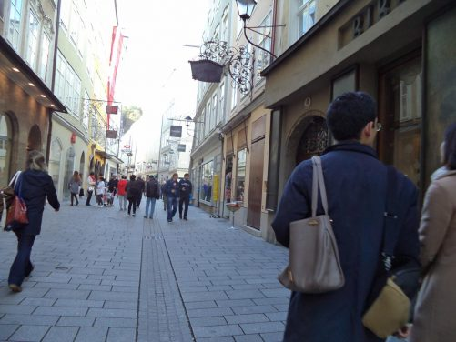 View along Getreidegasse, a long and narrow pedestrian street running parallel to the left bank of the river in the centre of the old town. It is famous for the old-style wrought iron signs that can be seen outside many of the shops.