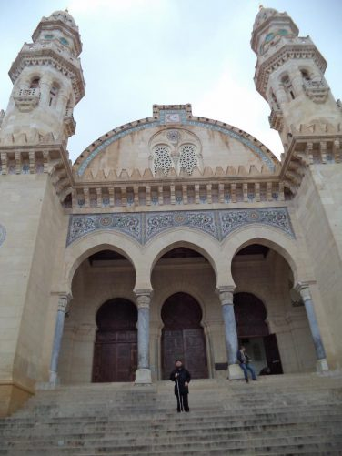 Tony half way up the 17 steps leading to the main entrance of Ketchaoua Mosque. Above the stone front façade with a pair of octagonal minarets flank either side of the entrance.