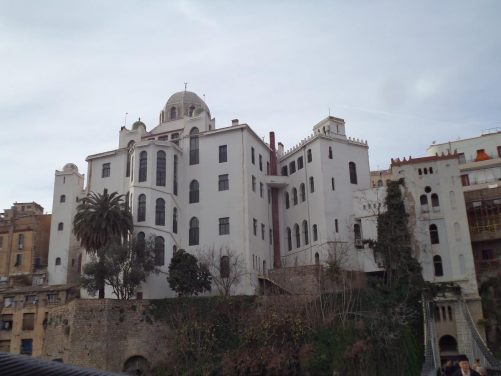 View from the Mellah Slimane Bridge with the large white-painted La Medersa (Madrasa) sitting prominently at the edge of the ravine. This madrasa, or religious school, opened in 1909.